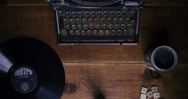 A typewriter and a vynal record rest on a wood desk.