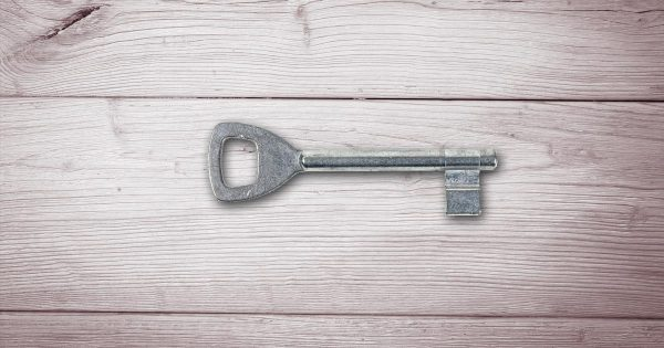 A simplistic vintage key rests on a wood table.