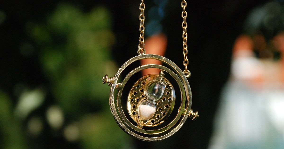 A golden necklace with three rotating circular parts and an hour glass in the middle. It is the time-turner from Harry Potter. The background is out of focus, but it is green.