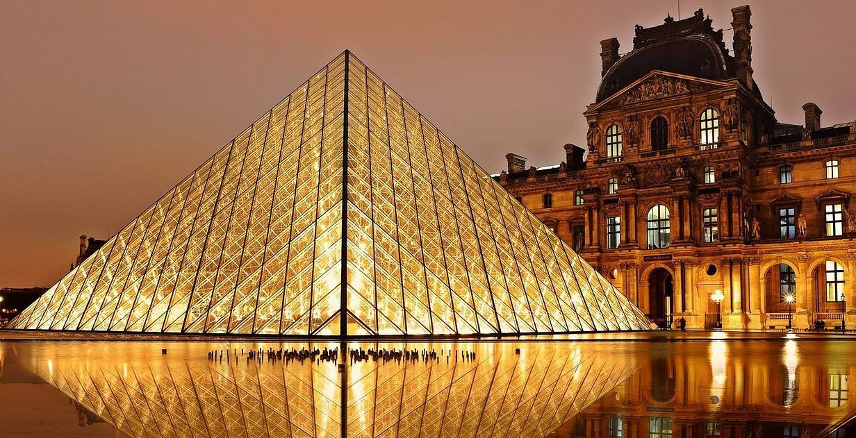 The Louvre in Paris at night. It is a rectangular stone building, and there are warm lights in the windows. A glass pyramid sits in front of it glowing with light and reflecting in the water of a large fountain.