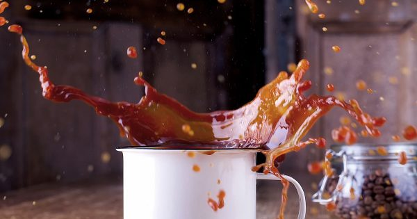 A coffee cup full of coffee is mid explosion and the coffee is flying everywhere across a table.