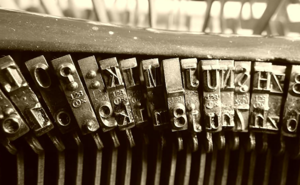 An assortment of metal letters for a printing press lined up against an out of focus metal background.