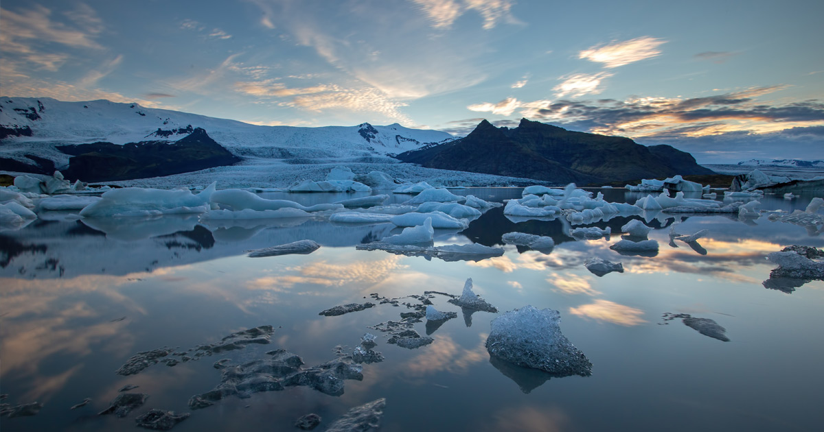 Ice covered mountains loom in the background, with ice and snow floating in the cold waters of the artic.