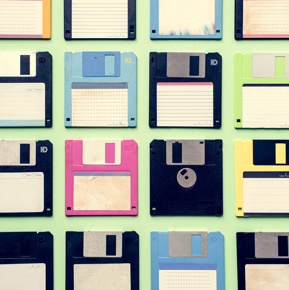 A variety of colourful floppy disks sit side by side on a pale green desktop.