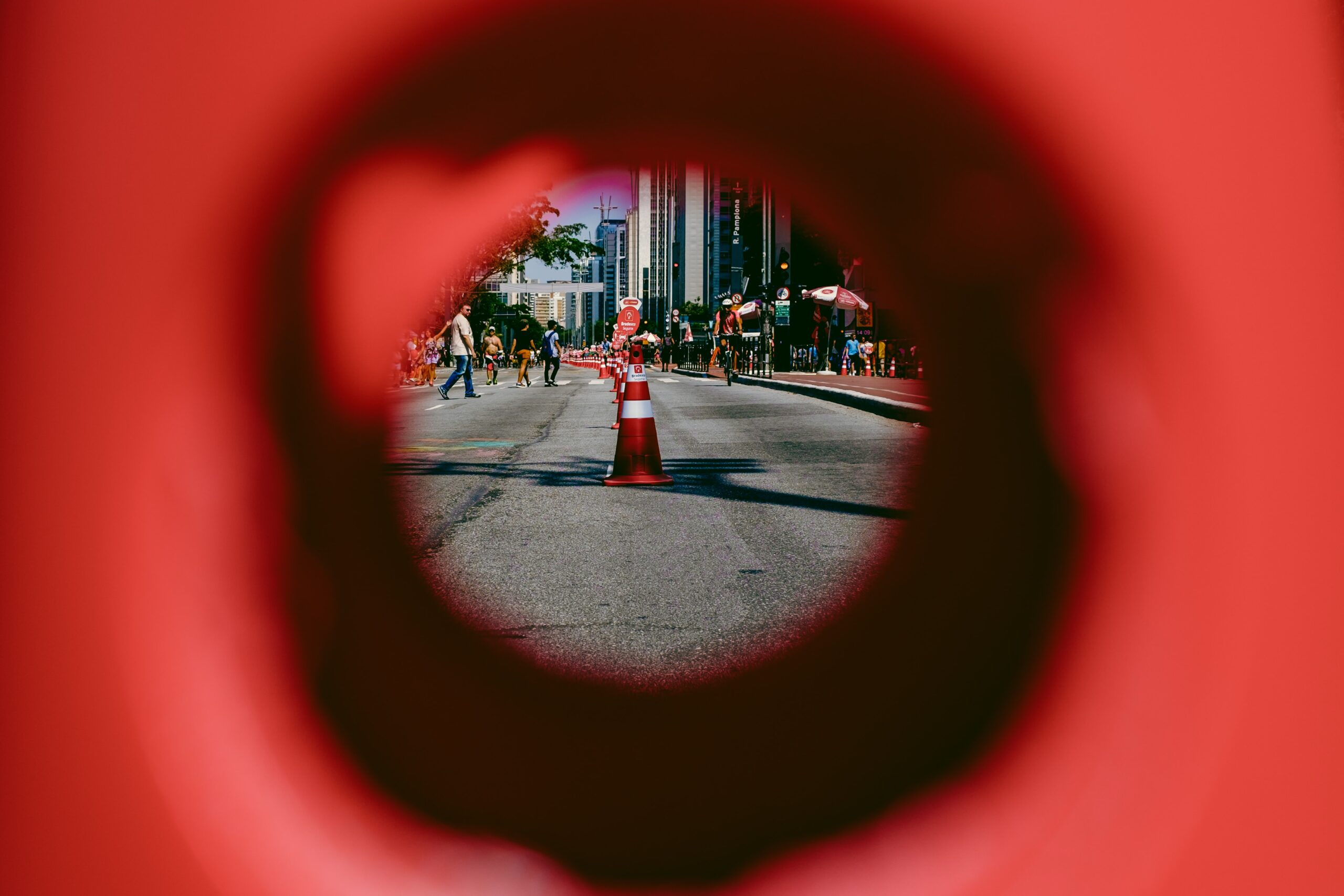 a view of a city street, with a pylon in the middle of the road, framed though the hole of a pylon